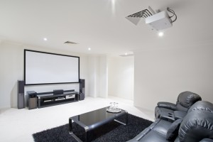 home theater room with black leather recliner chairs black rug and table with wine glasses